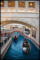 Couple kissing in gondola below bridge, Venetian casino. Las Vegas, Nevada, USA