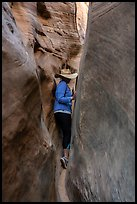 Woman squeezing in Zebra Slot Canyon. Grand Staircase Escalante National Monument, Utah, USA ( color)
