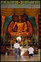 Men worshipping in front of a large Buddha state, Xa Loi pagoda, district 3. Ho Chi Minh City, Vietnam