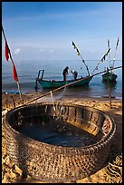 Fishermen pulling net out of circular basket. Phu Quoc Island, Vietnam (color)