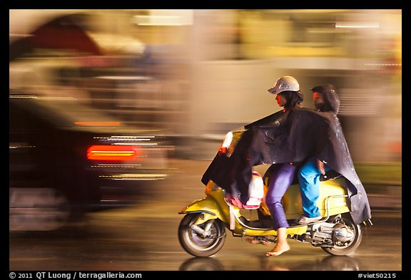 Women riding scooter in the rain. Ho Chi Minh City, Vietnam