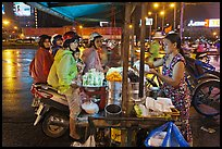 Women riding motorbikes buy sweet rice. Ho Chi Minh City, Vietnam ( color)