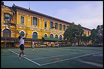 Men play tennis in front of colonial-area courthouse. Ho Chi Minh City, Vietnam (color)