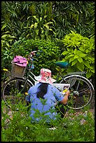 Woman reading newspaper next to bicycle in park. Ho Chi Minh City, Vietnam