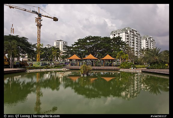 Reflecting pool, completed residential buildings, and crane, Phu My Hung, district 7. Ho Chi Minh City, Vietnam