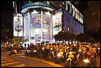 Dense motorcycle traffic in front of Saigon Center at night. Ho Chi Minh City, Vietnam