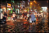 Traffic passes man pushing food cart on flooded street at night. Ho Chi Minh City, Vietnam