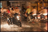 Man riding motorbike on flooded street seen against riders going in opposite direction. Ho Chi Minh City, Vietnam
