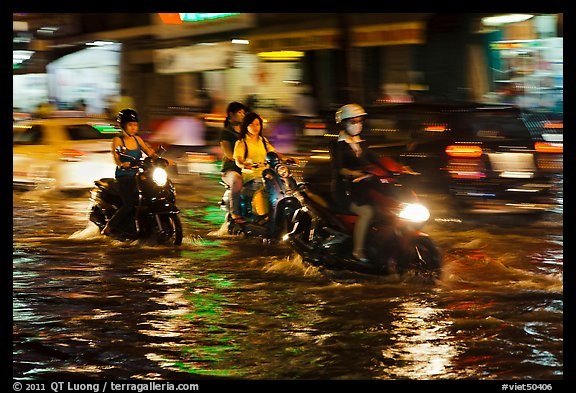 Women riding motorcyles at night in water. Ho Chi Minh City, Vietnam
