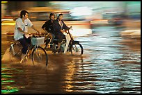Bicyle and motorbike riders on monsoon-flooded street. Ho Chi Minh City, Vietnam
