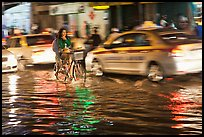 Women riding a bicycle on a flooded street at night. Ho Chi Minh City, Vietnam