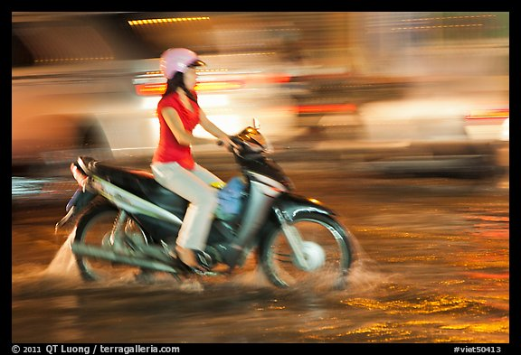 Woman riding on water-filled street, and light streaks. Ho Chi Minh City, Vietnam