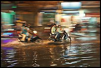 Motorcycles riding through the water on street with motion. Ho Chi Minh City, Vietnam