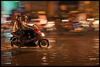 Couple sharing fast night ride on wet street. Ho Chi Minh City, Vietnam