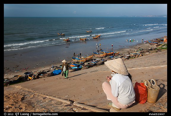 Woman on stairs overlooking beach with fishing boats. Mui Ne, Vietnam (color)