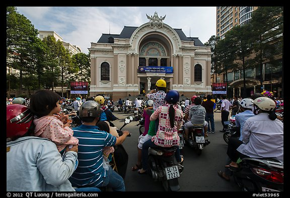Families gather on motorbikes to watch performance in front of opera house. Ho Chi Minh City, Vietnam (color)