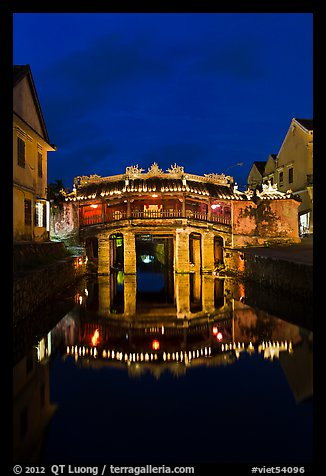 Illuminated Japanese covered bridge reflected in canal. Hoi An, Vietnam