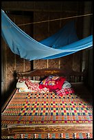Wooden bed with straw mat and mosquito net, Cam Kim Village. Hoi An, Vietnam (color)