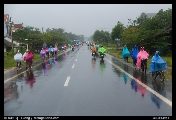 Riders wearing colorful ponchos on wet road on Hwy 1 south of Hue. Vietnam