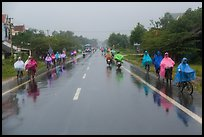 Riders wearing colorful ponchos on wet road on Hwy 1 south of Hue. Vietnam ( color)