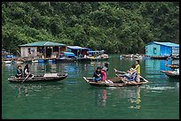Villagers move between floating houses by rowboat. Halong Bay, Vietnam ( color)