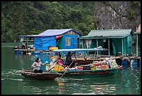 Woman buying produce from grocery boat, Vung Vieng village. Halong Bay, Vietnam ( color)