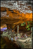 Tourists walking in cavernous chamber, Sungsot cave. Halong Bay, Vietnam ( color)