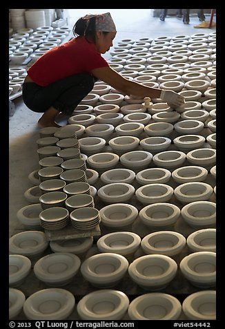 Woman laying ceramic bowls to dry in workshop. Bat Trang, Vietnam