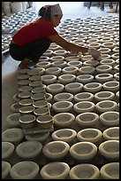 Woman laying ceramic bowls to dry in workshop. Bat Trang, Vietnam ( color)
