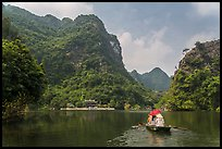 Boat journeying below tall lush cliffs, Trang An. Ninh Binh,  Vietnam ( color)