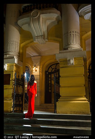 Woman in evening gown entering opera house. Hanoi, Vietnam
