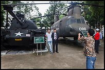 Tourists pose with tanks and helicopters, War Remnants Museum, district 3. Ho Chi Minh City, Vietnam ( color)
