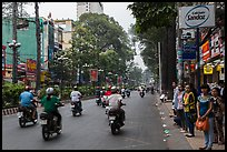 Motorbike traffic and pedestrians waiting for bus. Ho Chi Minh City, Vietnam