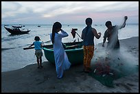 Fishermen folding net out of coracle boat as children watch. Mui Ne, Vietnam ( color)