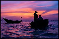 Men silhouetted paddling coracle boat at sunset. Mui Ne, Vietnam (color)