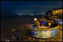 Man working on coracle boat at night. Mui Ne, Vietnam ( color)