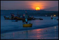 Fisherman paddling on coracle boat towards fishing boats at moonset. Mui Ne, Vietnam (color)