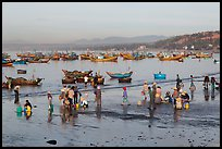 Hawkers gather on mirror-like beach in early morning. Mui Ne, Vietnam ( color)