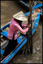 Woman in Ao Ba Ba holding from boat to bamboo poles. My Tho, Vietnam ( color)