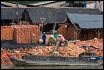 Workers loading bricks on boat. Sa Dec, Vietnam ( color)