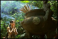 Tourist praying at an urn with incense near the entrance of Phong Nha Cave. Vietnam (color)