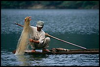 Fisherman retrieves net from a dugout boat. Northeast Vietnam (color)