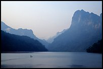 Dugout boat in Ba Be Lake, surrounded by tall cliffs, early morning. Northeast Vietnam