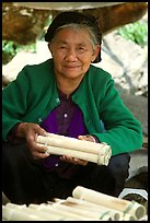 Woman selling sweet rice cooked in bamboo tubes. Vietnam (color)