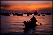 Man in a small boat, with moored boats seen against a vivid sunset. Vung Tau, Vietnam