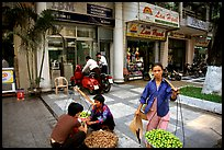 Old and new: street fruit vendors and computer store. Ho Chi Minh City, Vietnam (color)