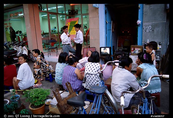 Watching TV on the street with the neighboors. Ho Chi Minh City, Vietnam (color)