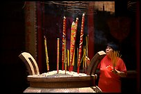Offering incense at a Chinese temple in Cho Lon. Cholon, District 5, Ho Chi Minh City, Vietnam (color)