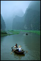 Villagers going by boat to their fields, amongst misty cliffs, Tam Coc. Ninh Binh,  Vietnam
